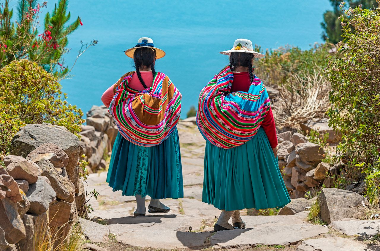 Two indigenous Quechua women in traditional clothes walking down the path to the harbor of Isla Taquile (Taquile Island) with the Titicaca Lake in the background, Peru., Uros Islands