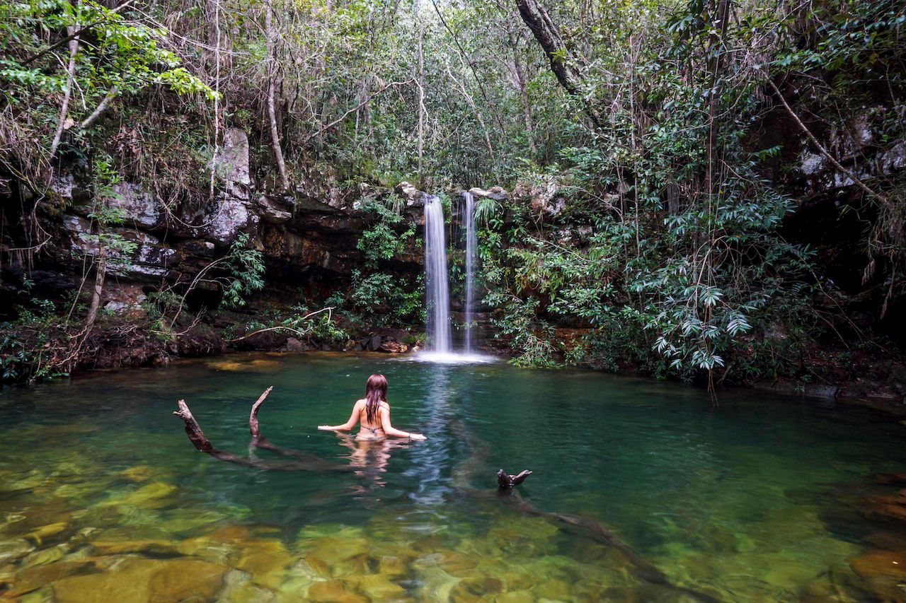 Woman,Standing,In,A,Fallen,Tree,In,Loquinhas,Waterfall,(cachoeira, Chapada dos Veadeiros