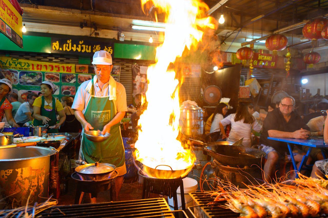 Bangkok, Thailand - January 26, 2019 : Street food chef cooking with fire at Yaowarat road in Bangkok, day two in bangkok