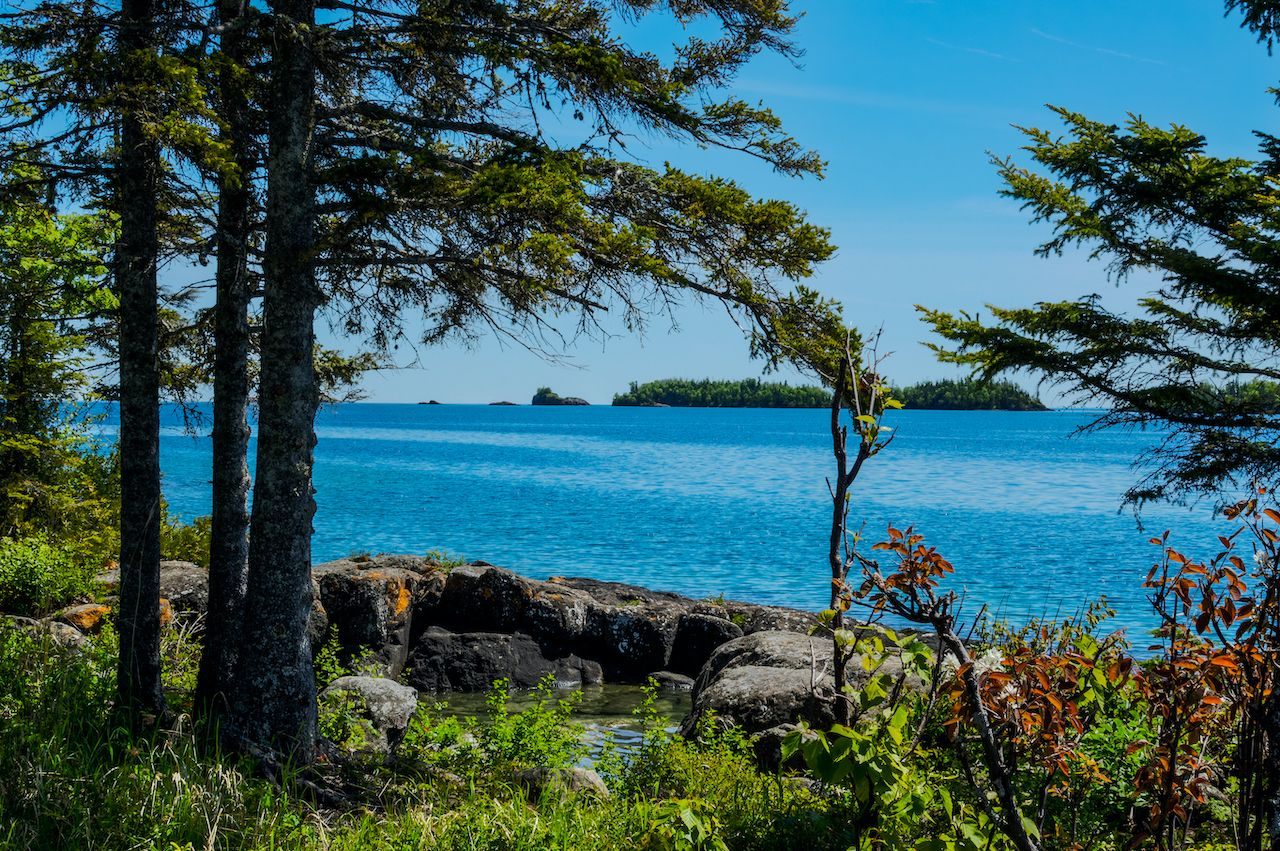 A view through the forest shows several of the tiny islands off the main island of Isle Royale NP in Lake Superior  off Copper Harbor, MI. Large boulders  surround a little water pool on shoreline., Scuba diving in Isle Royale