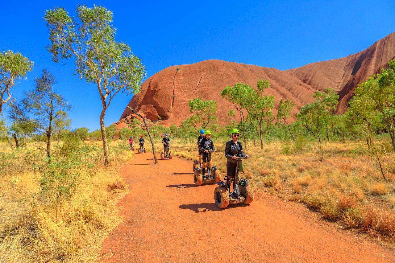 Uluru, Northern Territory, Australia - Aug 24, 2019: people visit Ayers Rock with Uluru Segway Tours along Uluru Base Walk in sand path of Uluru-Kata Tjuta National Park. Outdoors activity., The Red Centre Way