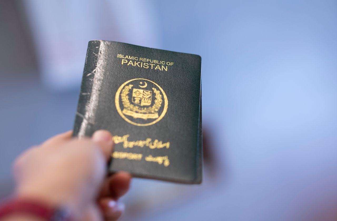 A hand holds passport of Pakistan. Focus on the letters on passport., weakest passports