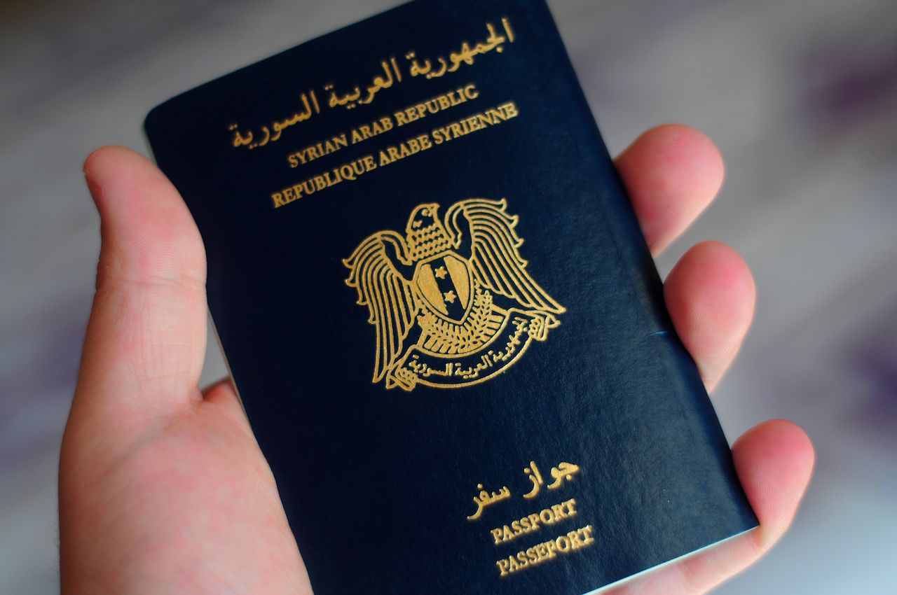 A hand carrying a Syrian passport, weakest passports
