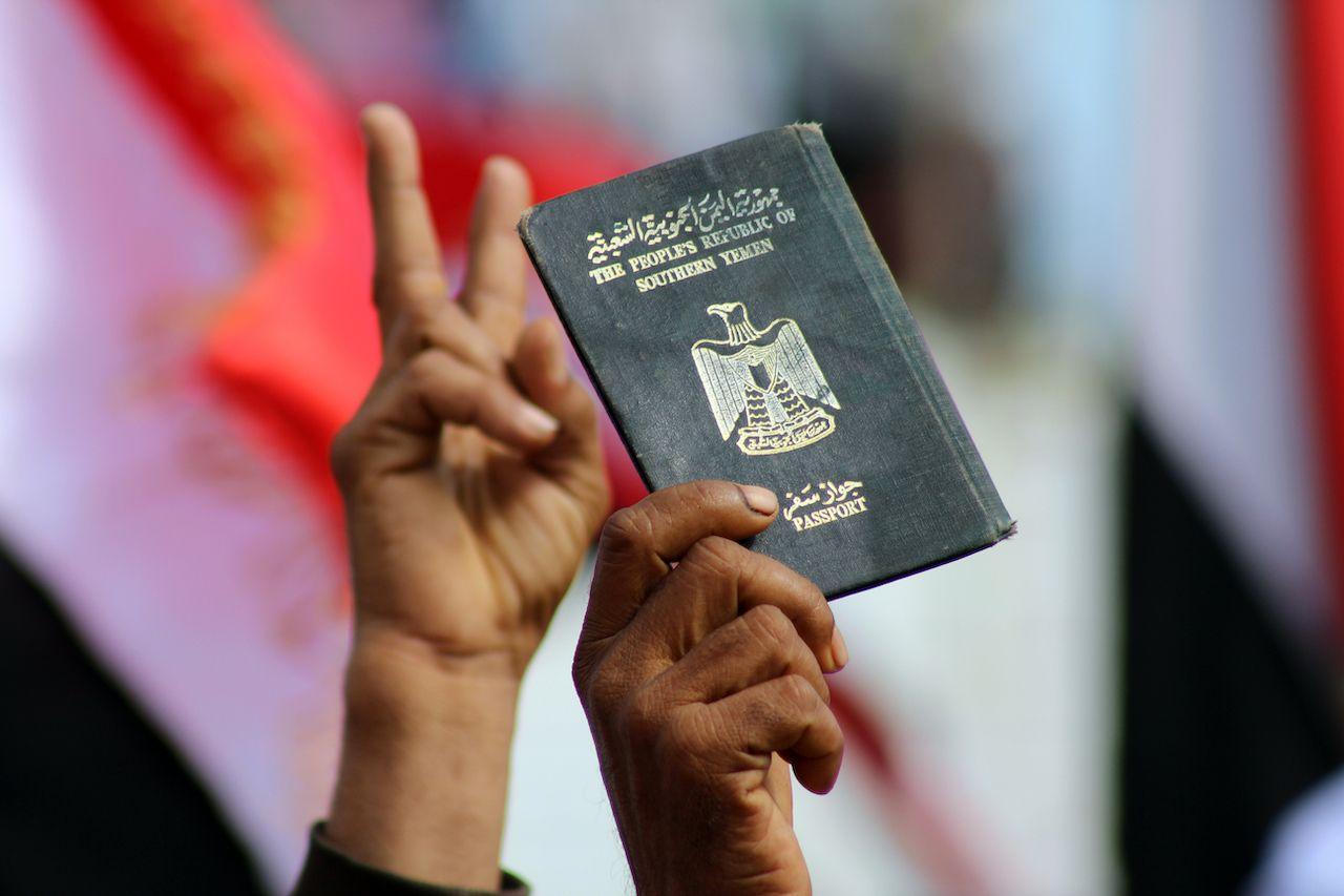 Aden, South Yemen-30Nov2014- A Southern Yemeni protester raising a passport of the People's Republic of South Yemen, weakest passports