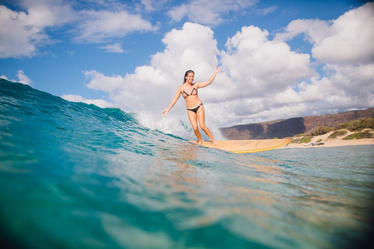 girl surfing in water in Hawaii, US Olympic surf team