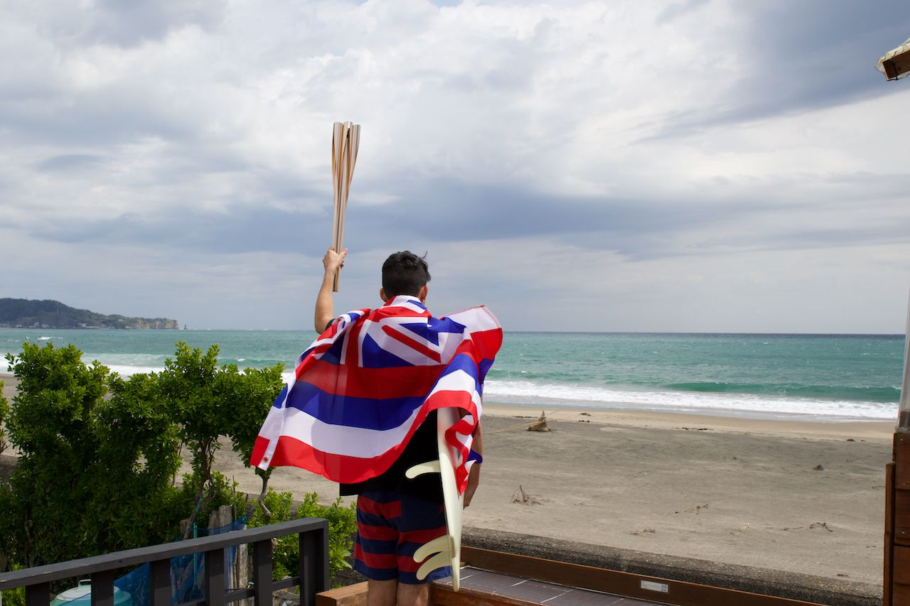 Man standing holding a flaming torch used in a large sporting event, with a surfboard and Hawaiian Flag looking at the Pacific Ocean in Chiba Japan where a big surfing competition is held., US Olympic surf team