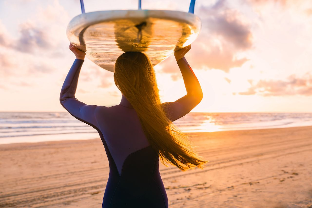 Surf girl with long hair go to surfing. Woman with surfboard on a beach at sunset or sunrise. Surfer and ocean, more sharks