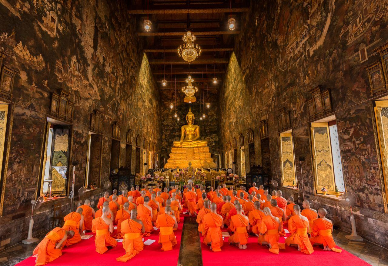 Bangkok, Thailand - July 20, 2016: Buddhist Monks praying and pay respect to the Buddha image at Wat Suthat on Buddhist Lent Day. The Buddhist Lent Day is The First Day of Rainy Season Retreat, bangkok events