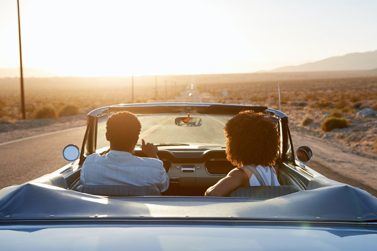 Rear,View,Of,Couple,On,Road,Trip,Driving,Classic,Convertible, Return of travel