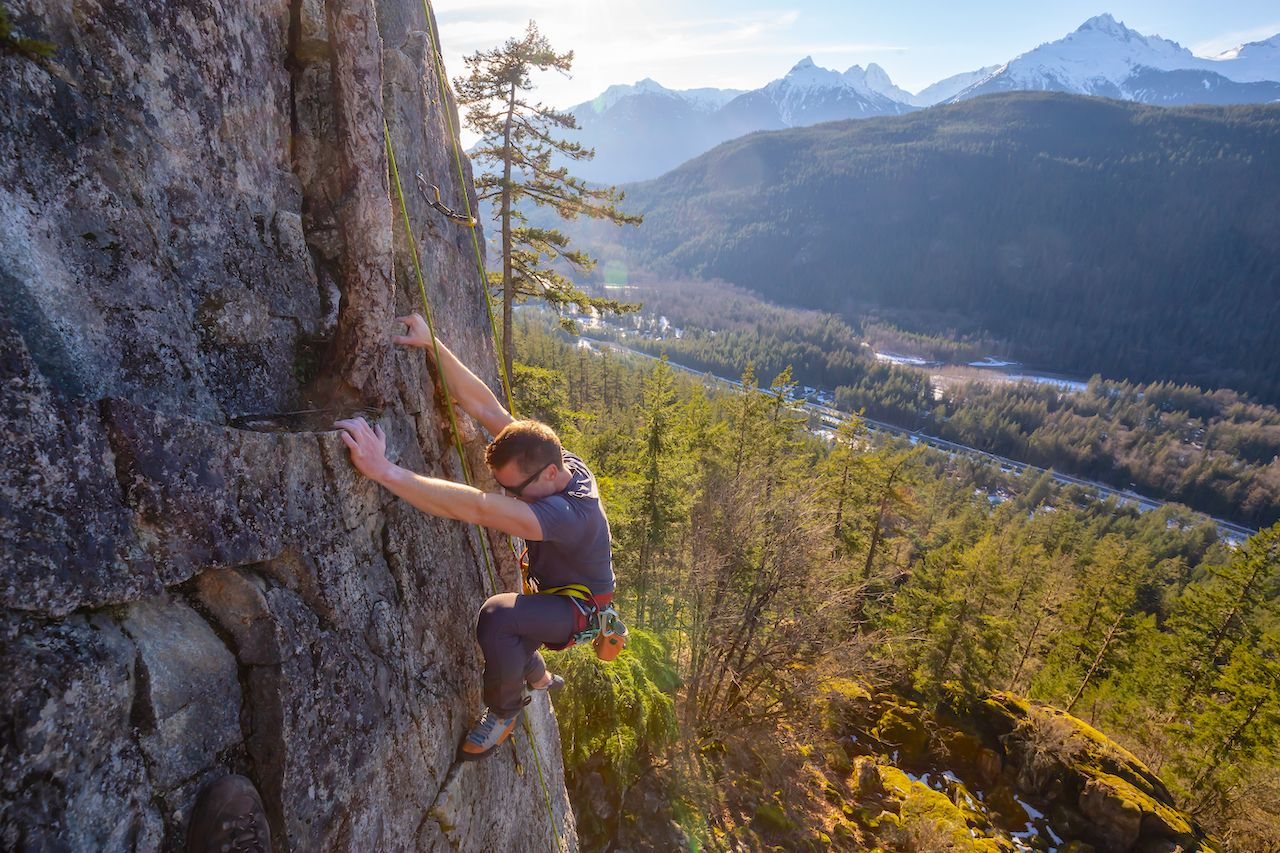 Male Rock climber climbing on the edge of the cliff during a sunny winter sunset. Taken in Area 44 near Squamish and Whistler, North of Vancouver, BC, Canada.,  British Columbia climbing