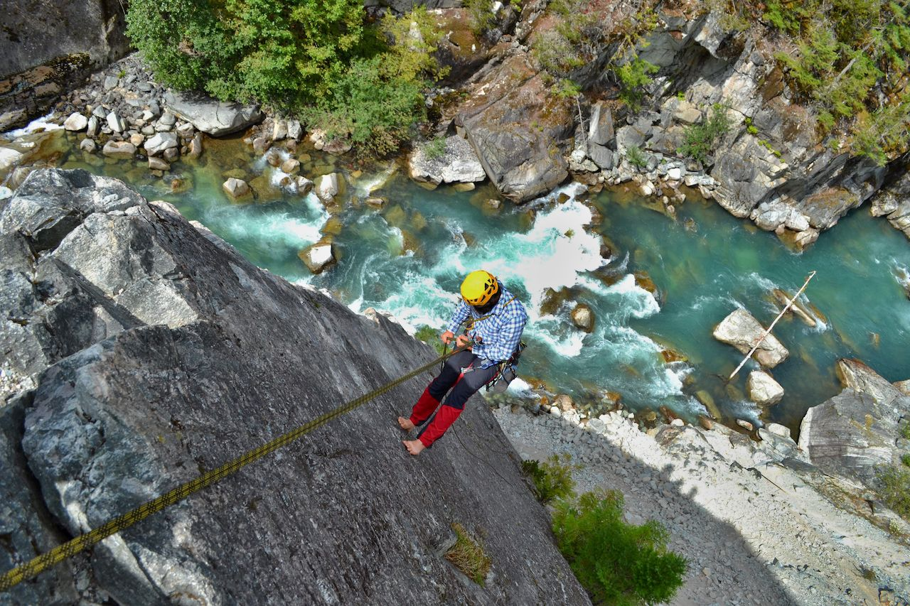 Climbing the majestic Star Chek multi-pitch route south of Whistler. Young man rappels beautiful climbing route above the wild river.,  British Columbia climbing