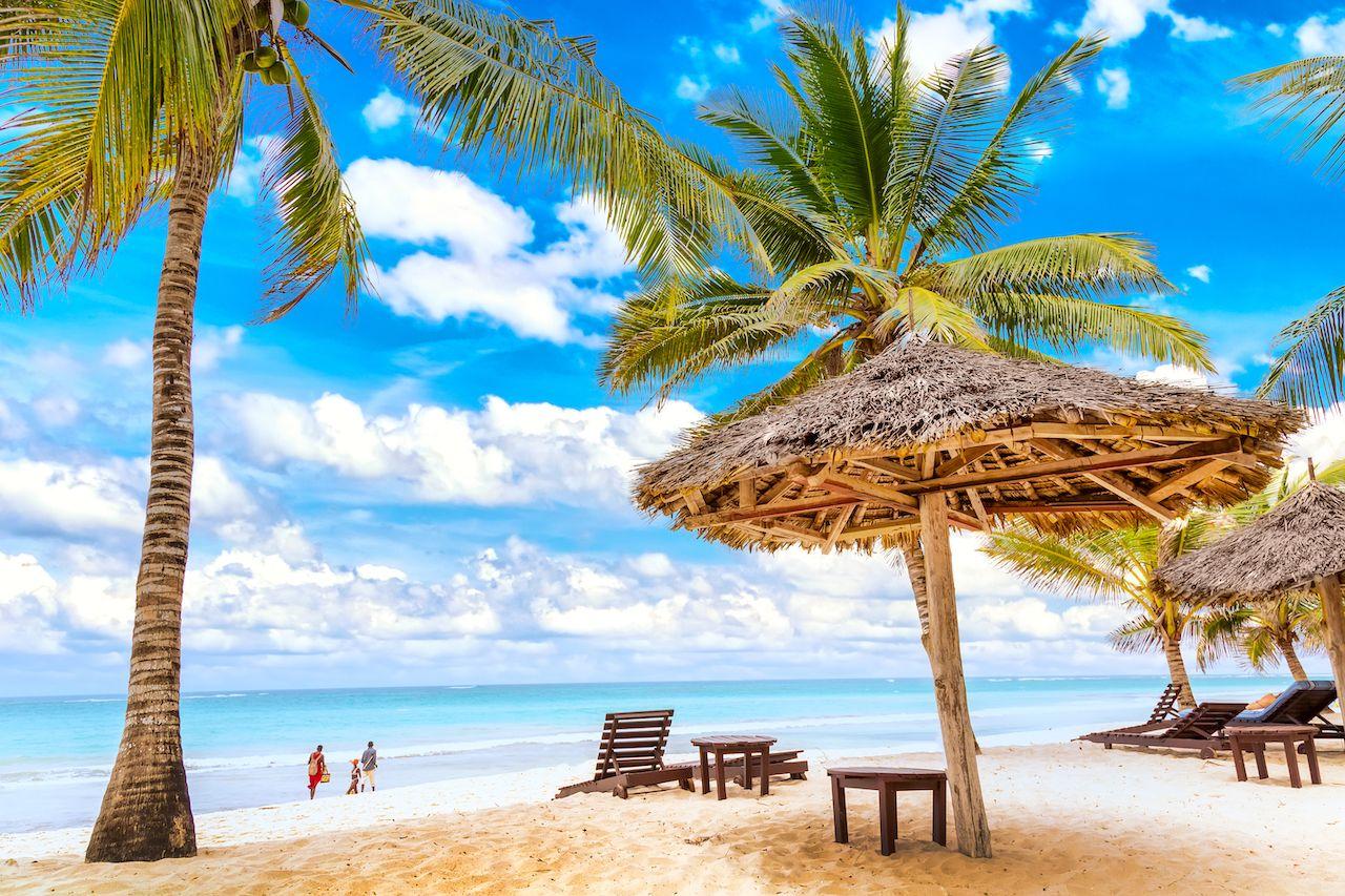 Sun,Loungers,Under,Umbrella,And,Palms,On,The,Sandy,Beach