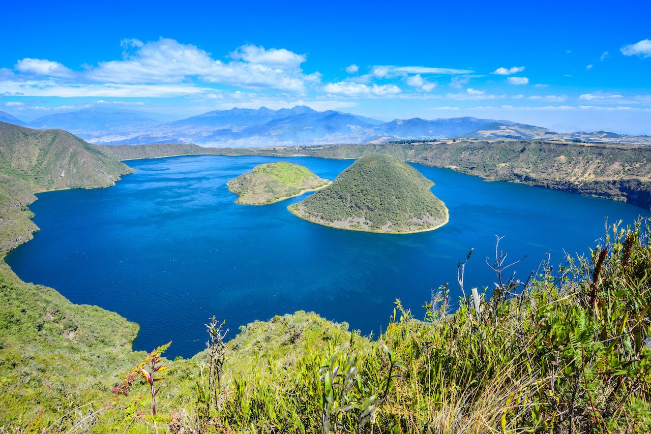 Cuicocha Crater Lake with its islands in the middle and bright blue water with bright blue sky