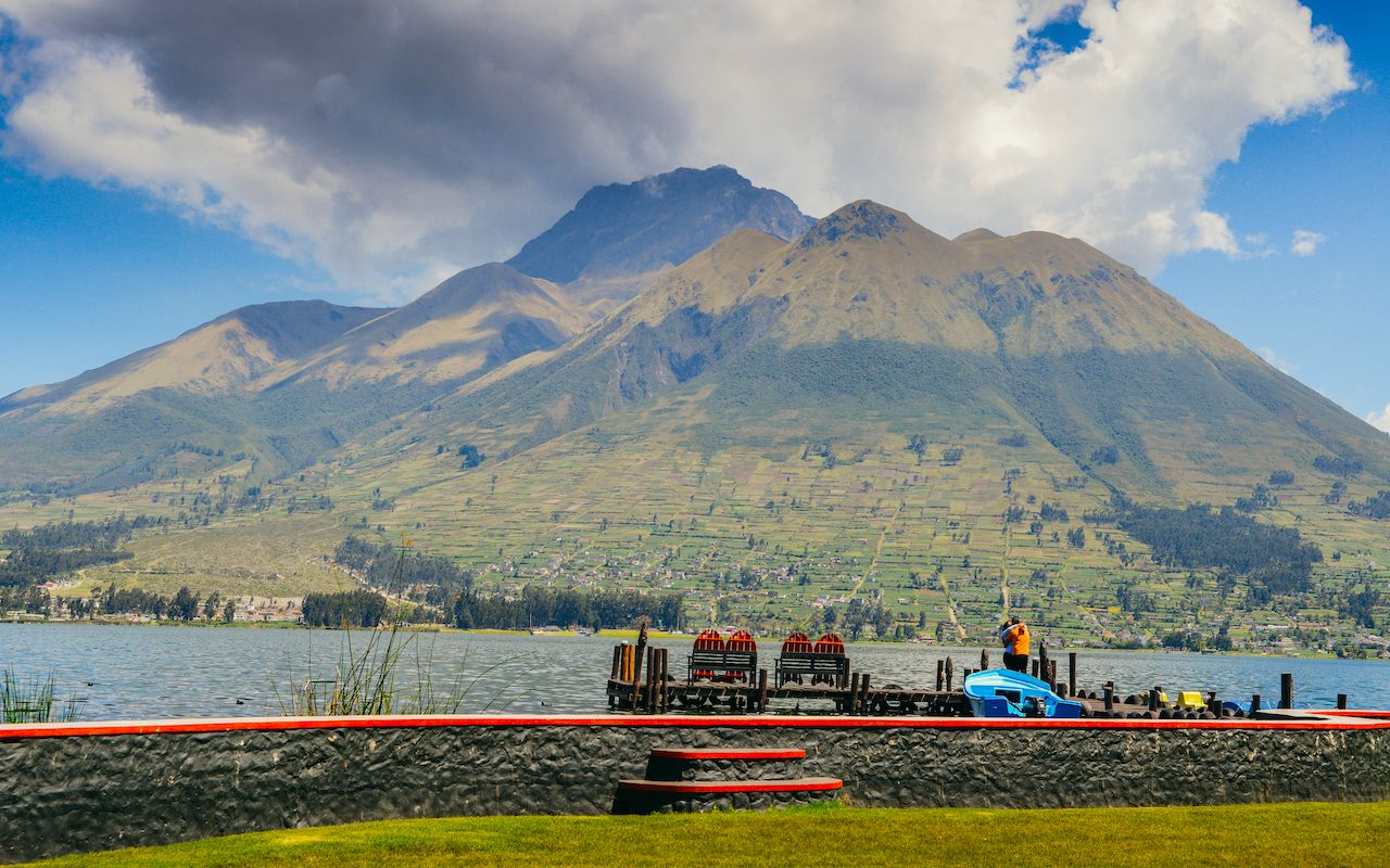 A couple hugs in front of San Pablo Lake, with the volcano in background in Ecuador