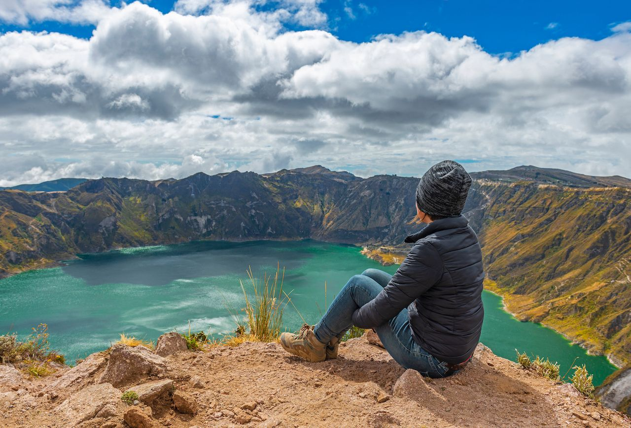 Woman staring at beautiful green-blue water of a volcanic crater lake in Ecuador