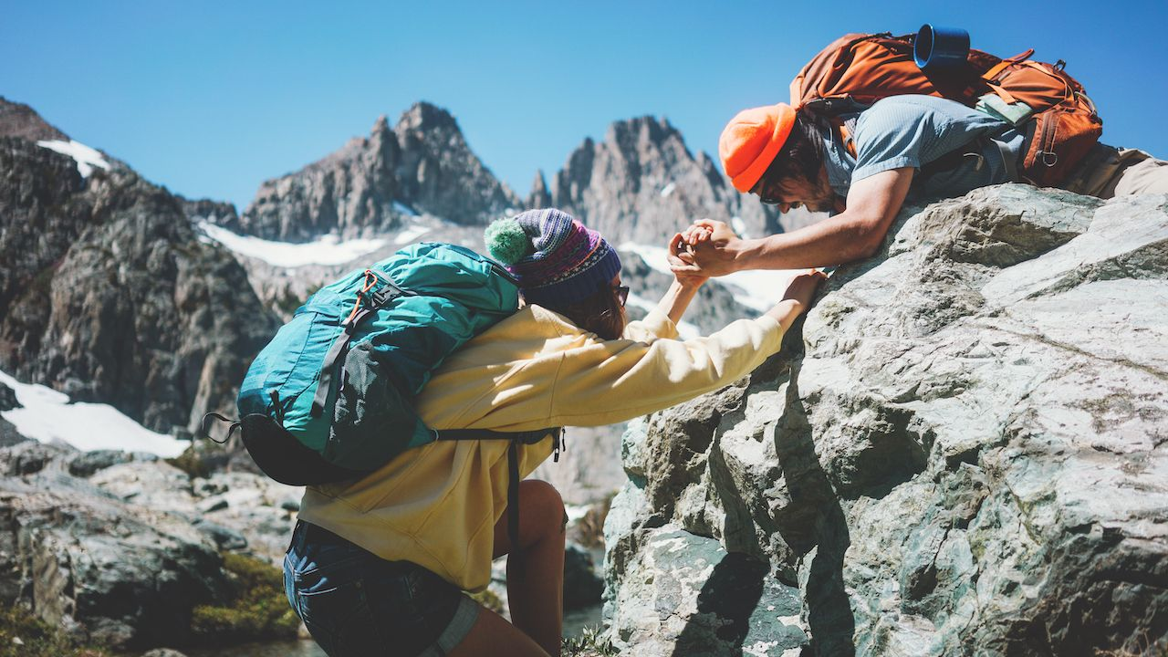Traveler,Helping,His,Friend,To,Climb,A,Rock.,Young,Active