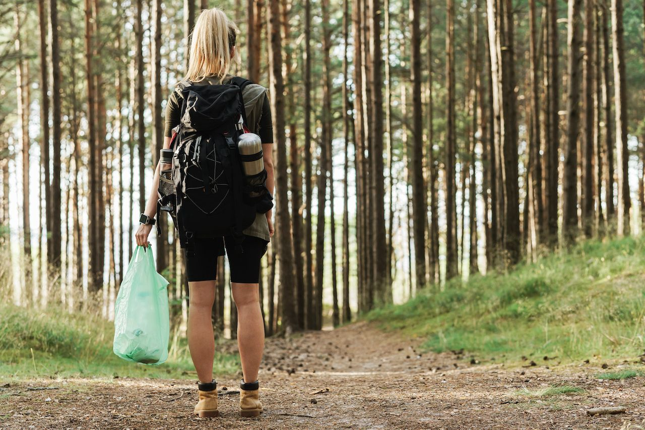 Young,Female,Hiker,With,A,Backpack,Collecting,Plastic,Waste,In
