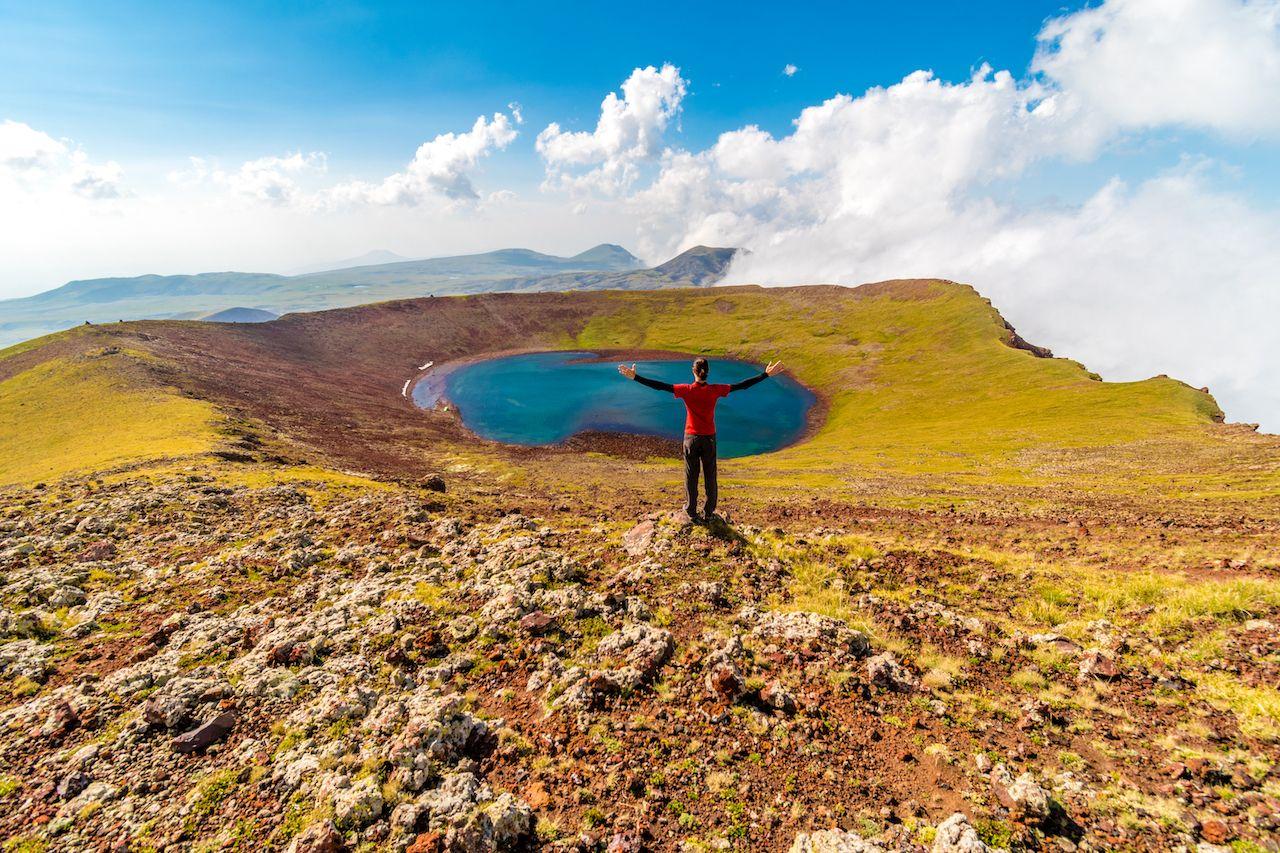 Man on a summit of Azhdahak volcano watching crater lake, Geghama mountains, Armenia, Transcaucasian Trail