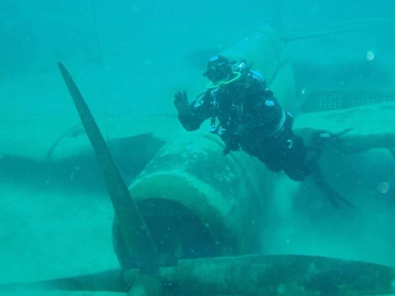 Scuba diver waves at camera net to the propellor of a submerged airplane at Dutch Springs, Pennsylvania