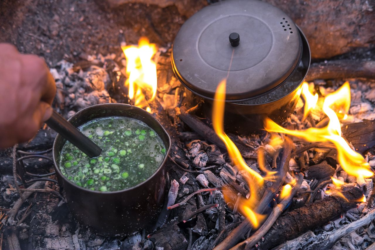 Two titanium pots sit in a fire cooking food for dinner. A hand stirs the pea soup with a long spoon., backpacking food