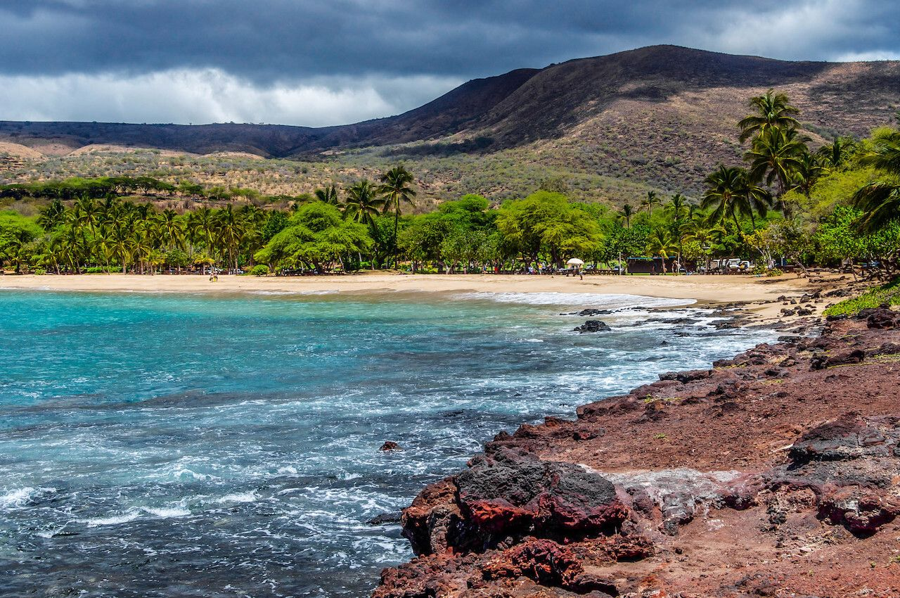 A view of the mountains of the island of Lanai, Hawaii and a secluded public beach as viewed from Flat Rock.,