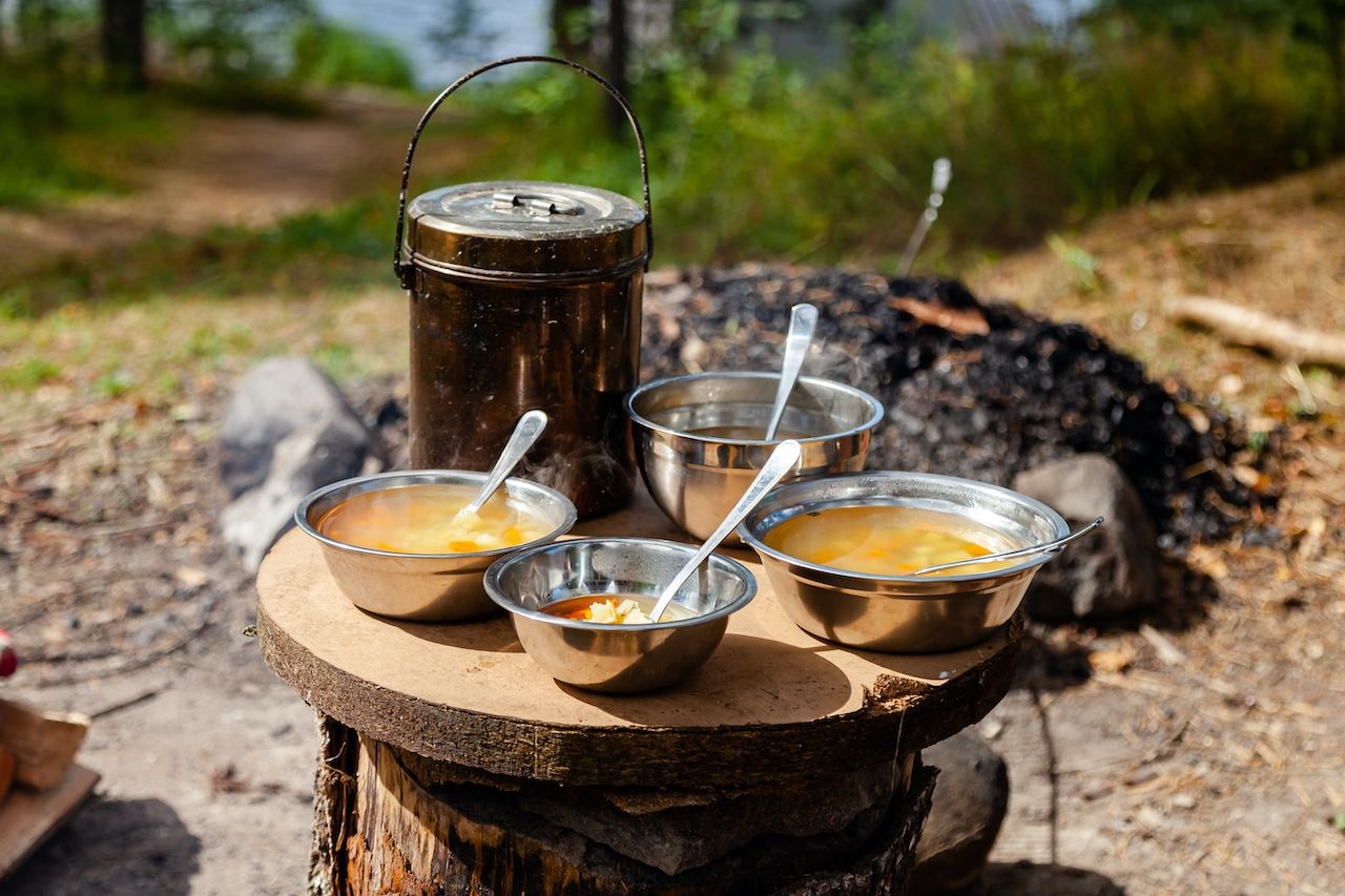 Lunch break at camp. Cooking simple delicious soup on fire, serving in touristic metal bowls. Concept of food preparation in travelling, camping, trekking, hiking trips. Bowler pot on background, backpacking food