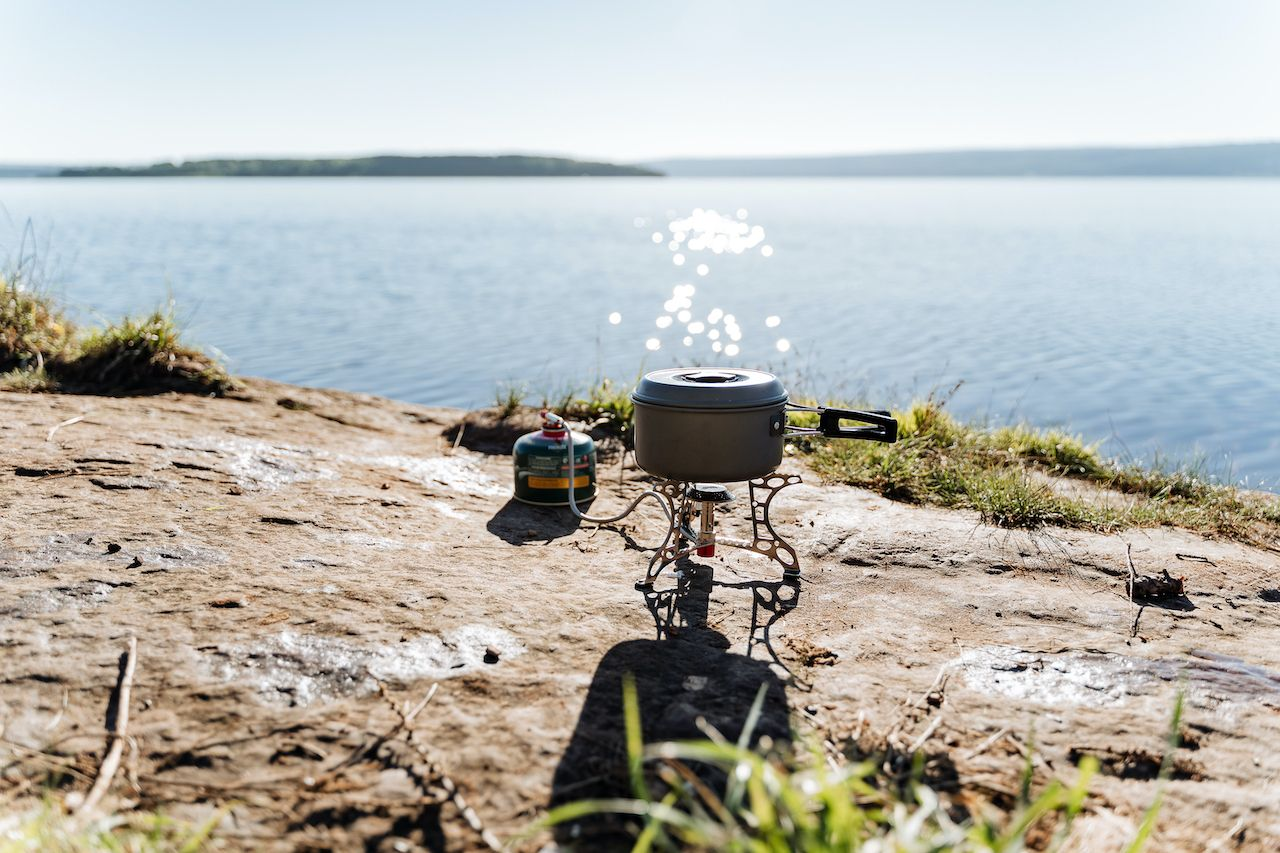 cooking on a gas burner in nature, gas camping stove for cooking food, aluminum pot with lid for trekking, camping equipment for cooking., backpacking food