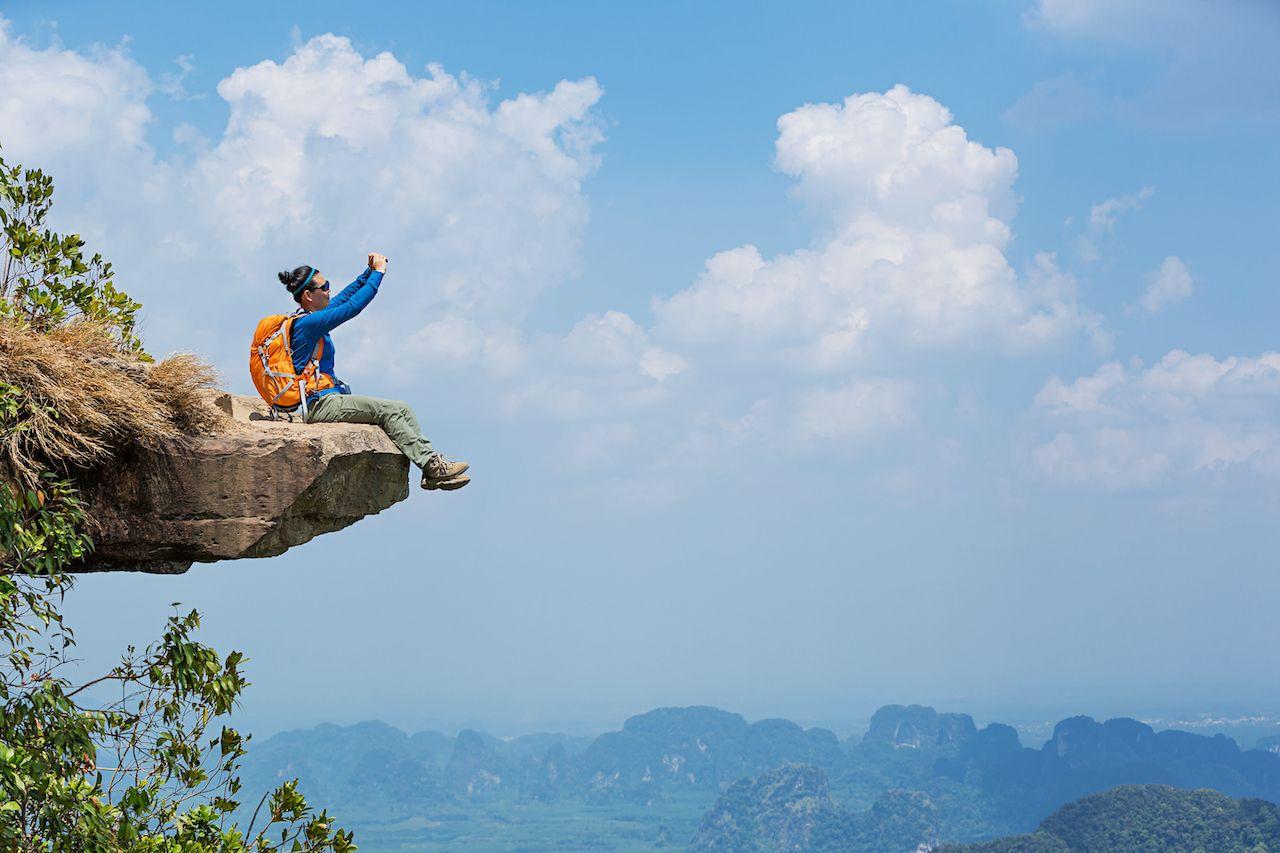Successful,Woman,Hiker,Taking,Photo,With,Smartphone,On,Mountain,Peak