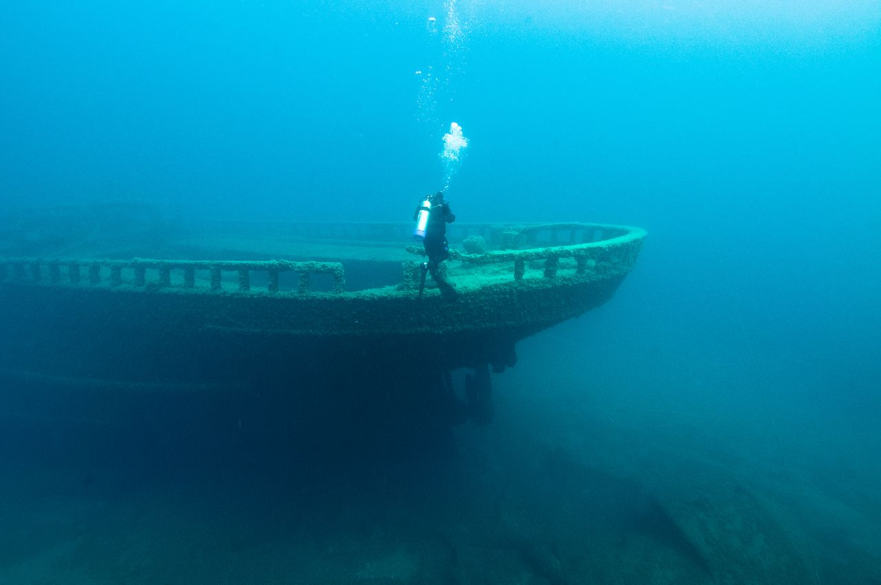 A diver inspects the bow of the wreck of the steel bulk freighter Grecian, where it rests in Lake Huron's Thunder Bay National Marine Sanctuary