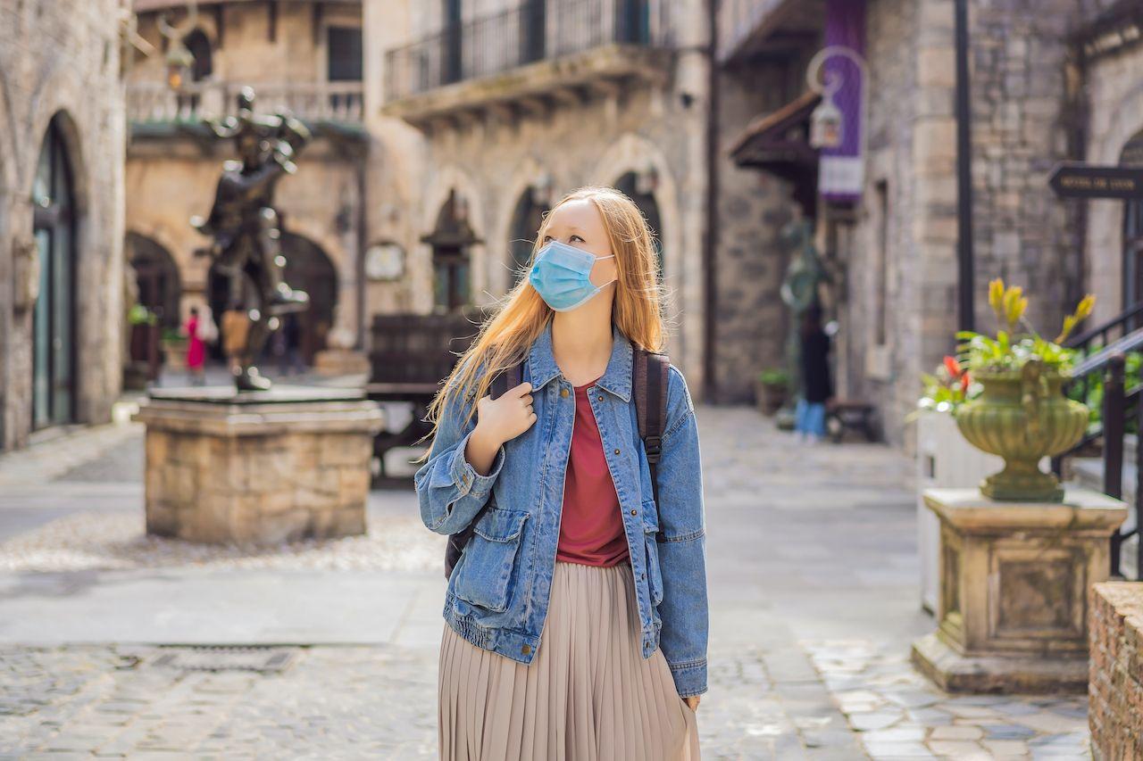woman in mask walking old european street