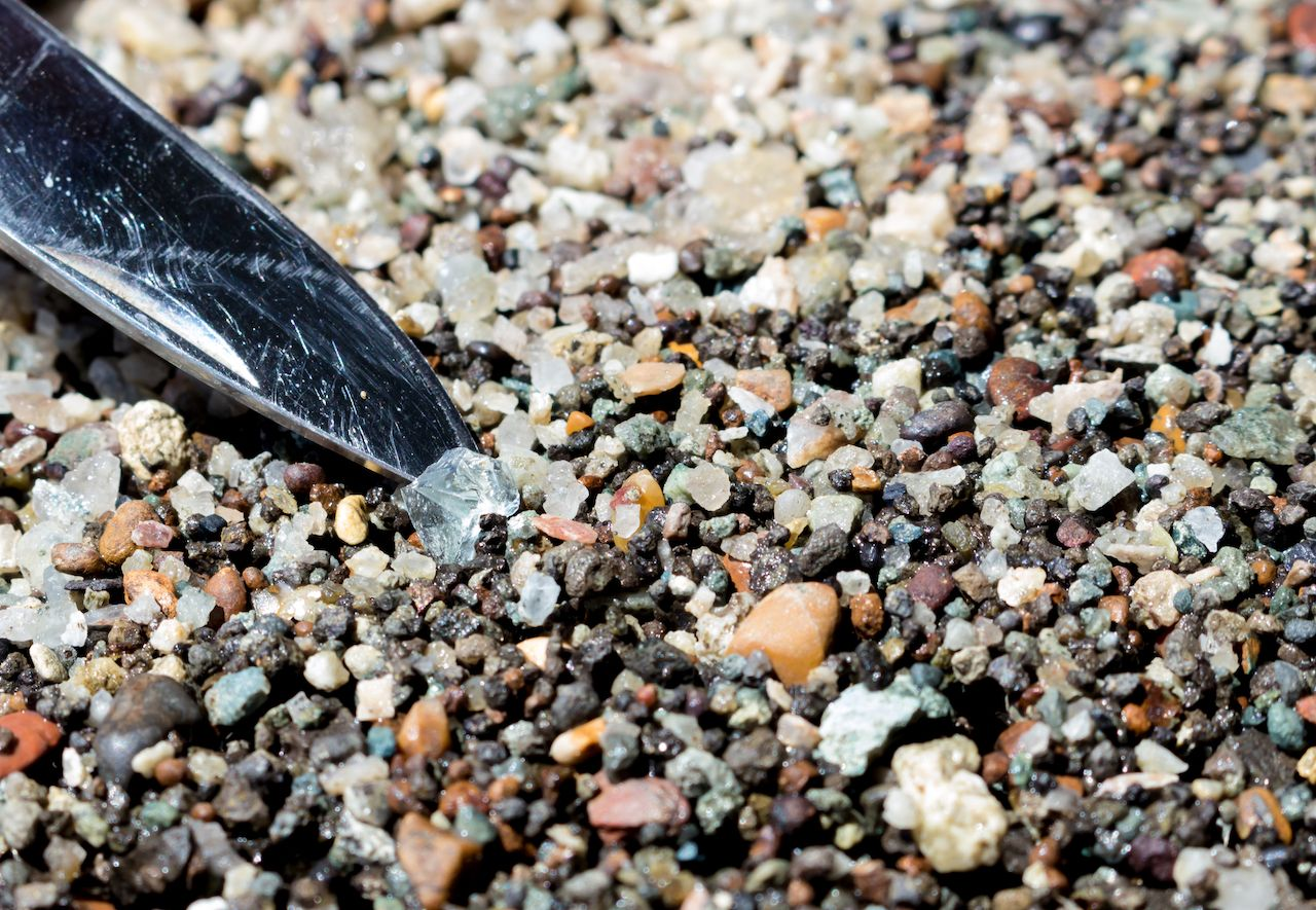 Close up of a lifting a piece of clear stone out of many tiny pebbles. Diamond hunting at Crater of Diamonds State Park.