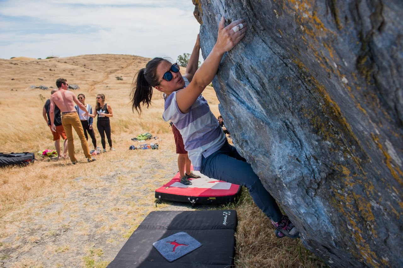 Young woman tackles a boulder climbing at Ring Mountain while other climbers talk in background