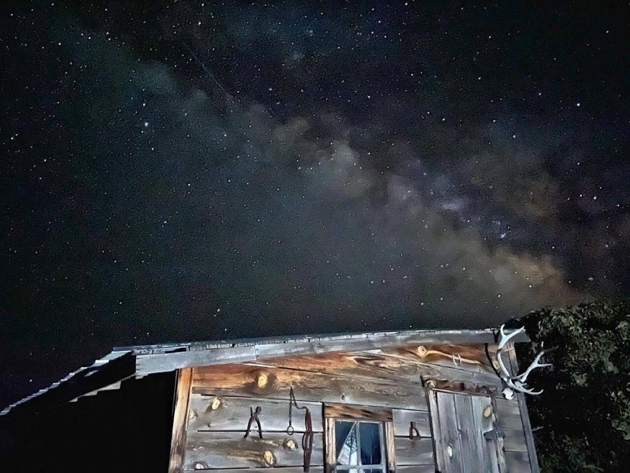Dark sky with trace of Milky Way behind an old wooden shed