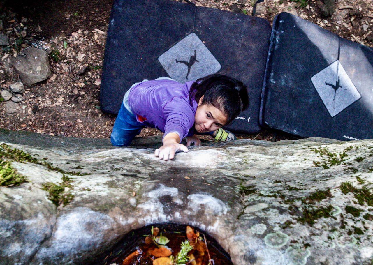 Young woman seen from above as she climbs a boulder