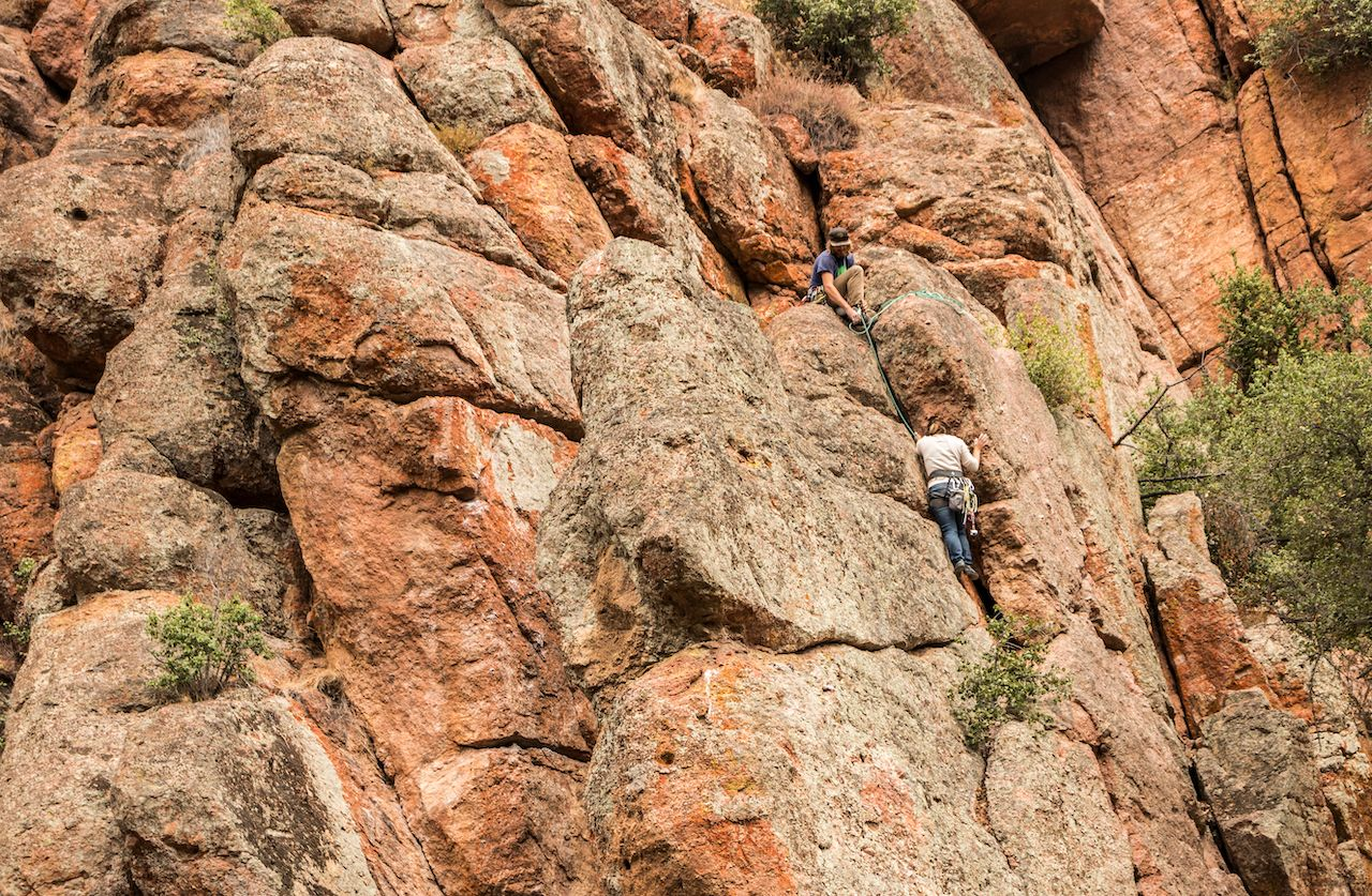 Two climbers scale a tall wall at Pinnacles National Park, Pacines, California, USA - October 11, 2018: Rock Climbing at Pinnacles National Park, California