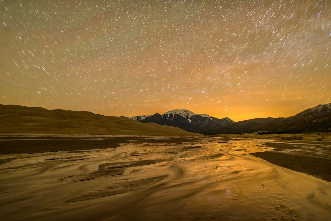 Long exposure captures star trails in night sky above spring Medano Creek and snow-capped peaks and sand dunes at Great Sand Dunes National Park.