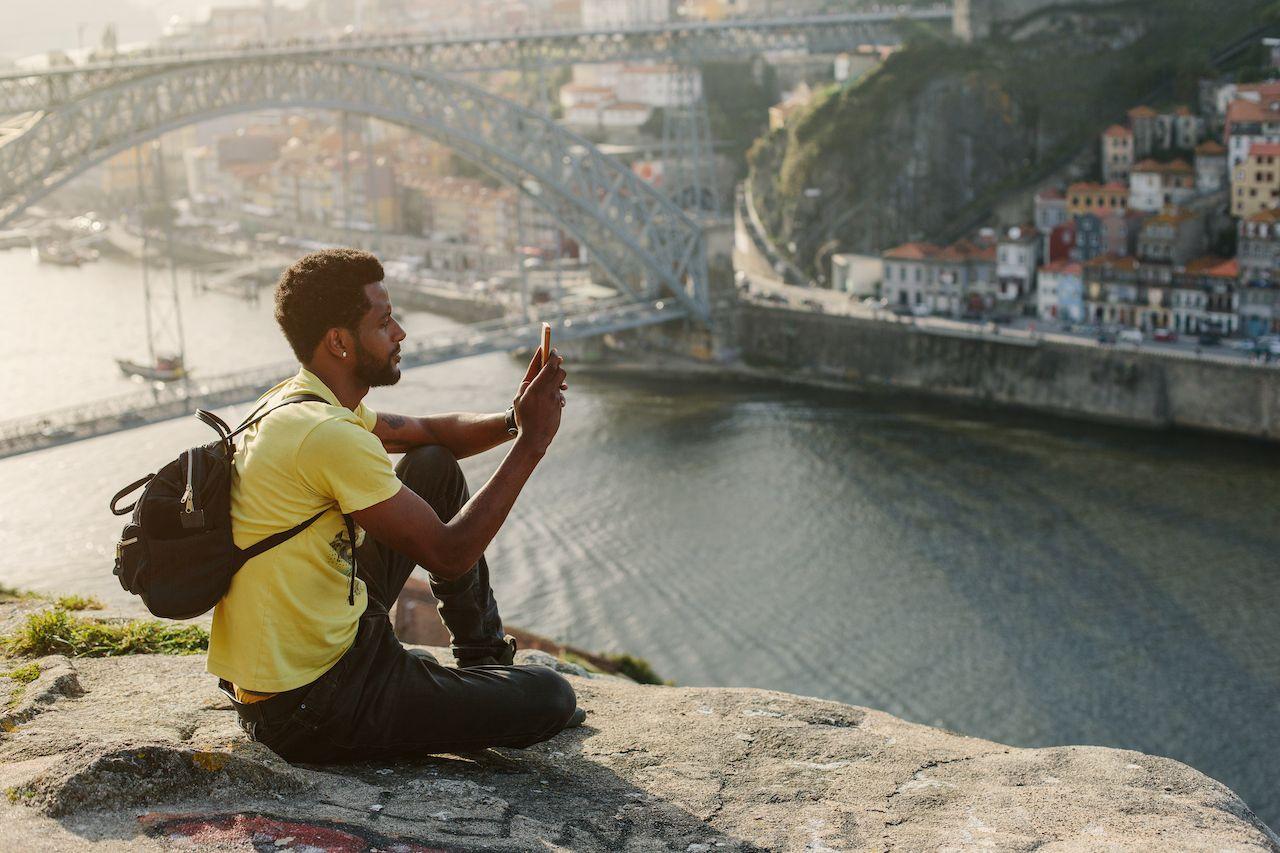 Traveler man doing photo on mobile phone.