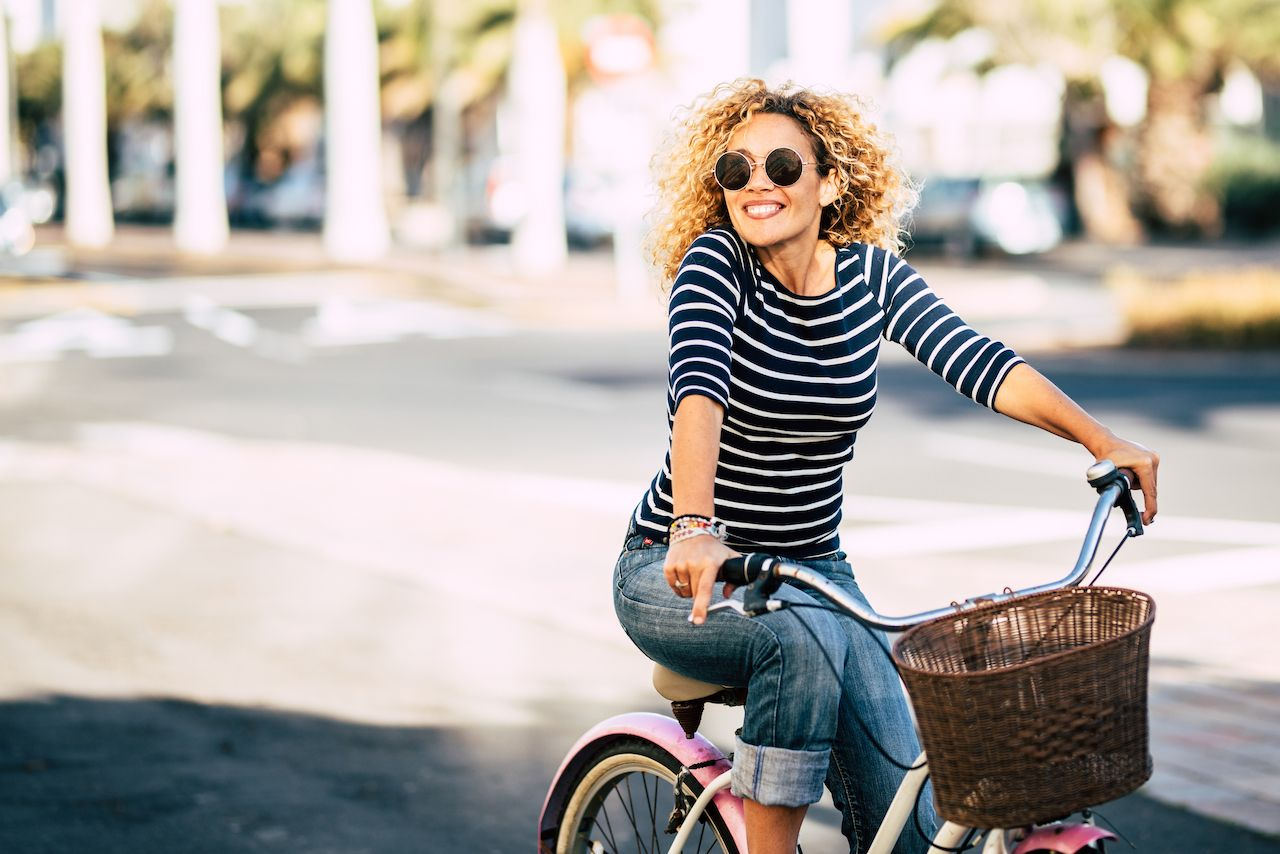 Beautiful and cheerful adult young woman enjoy bike ride in sunny urban outdoor leisure activity in the city