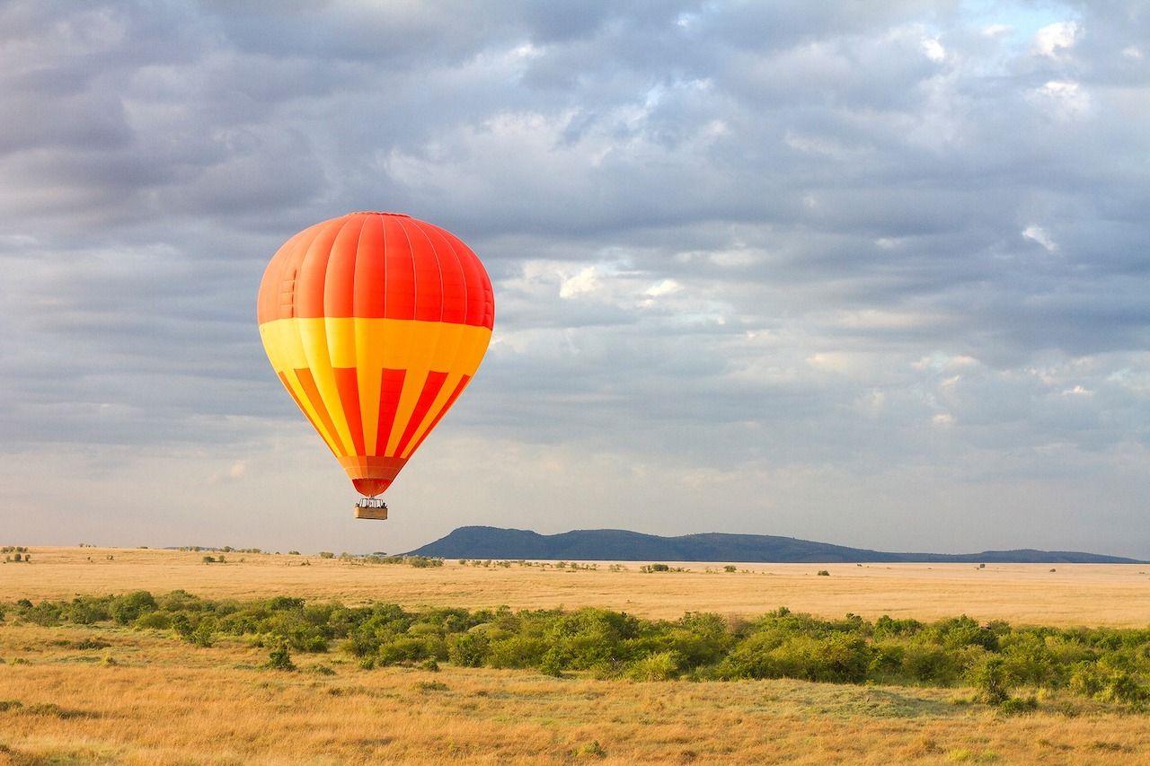 Orange hot air balloon above the Kenyan savannah