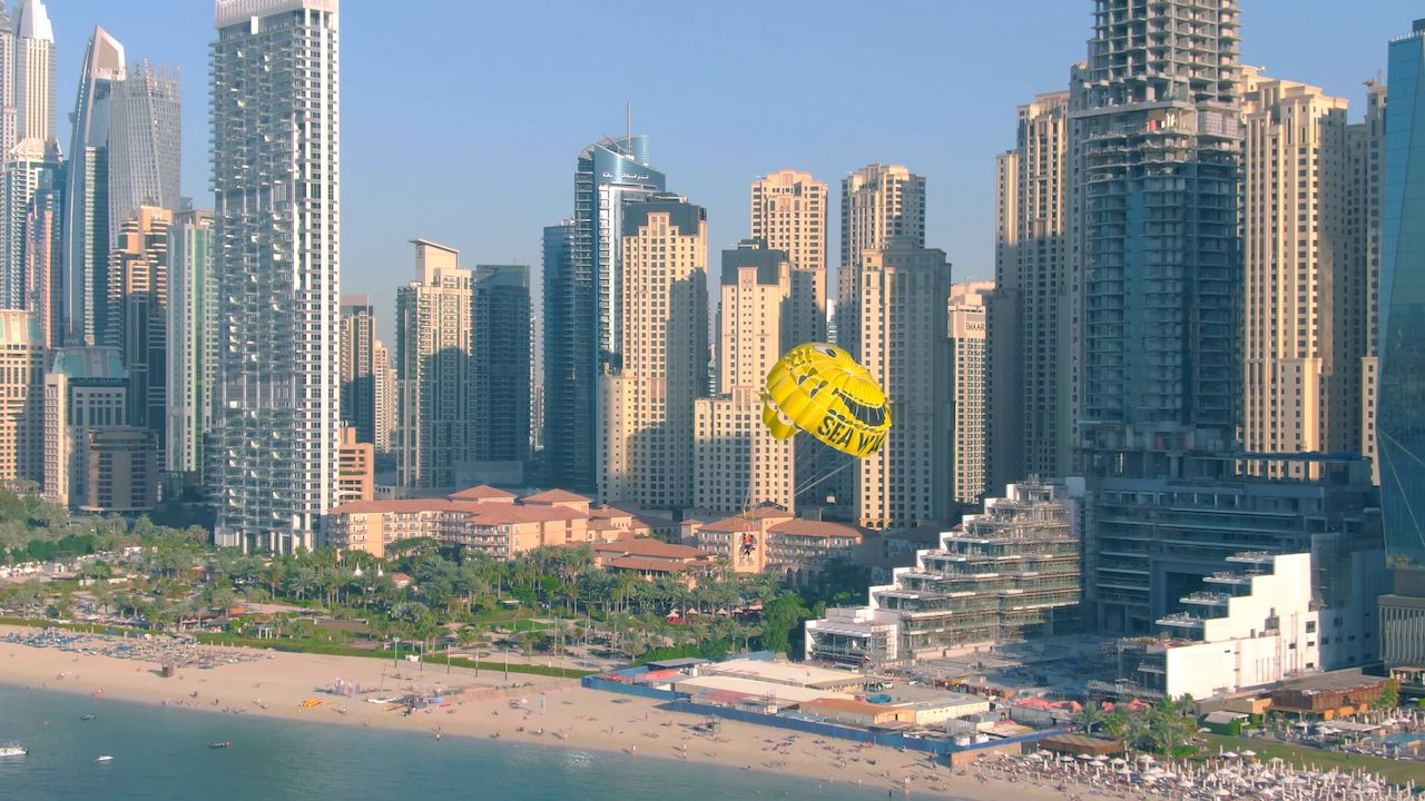 Aerial shot of SeaWake parasailing on skyscrapers and beach background