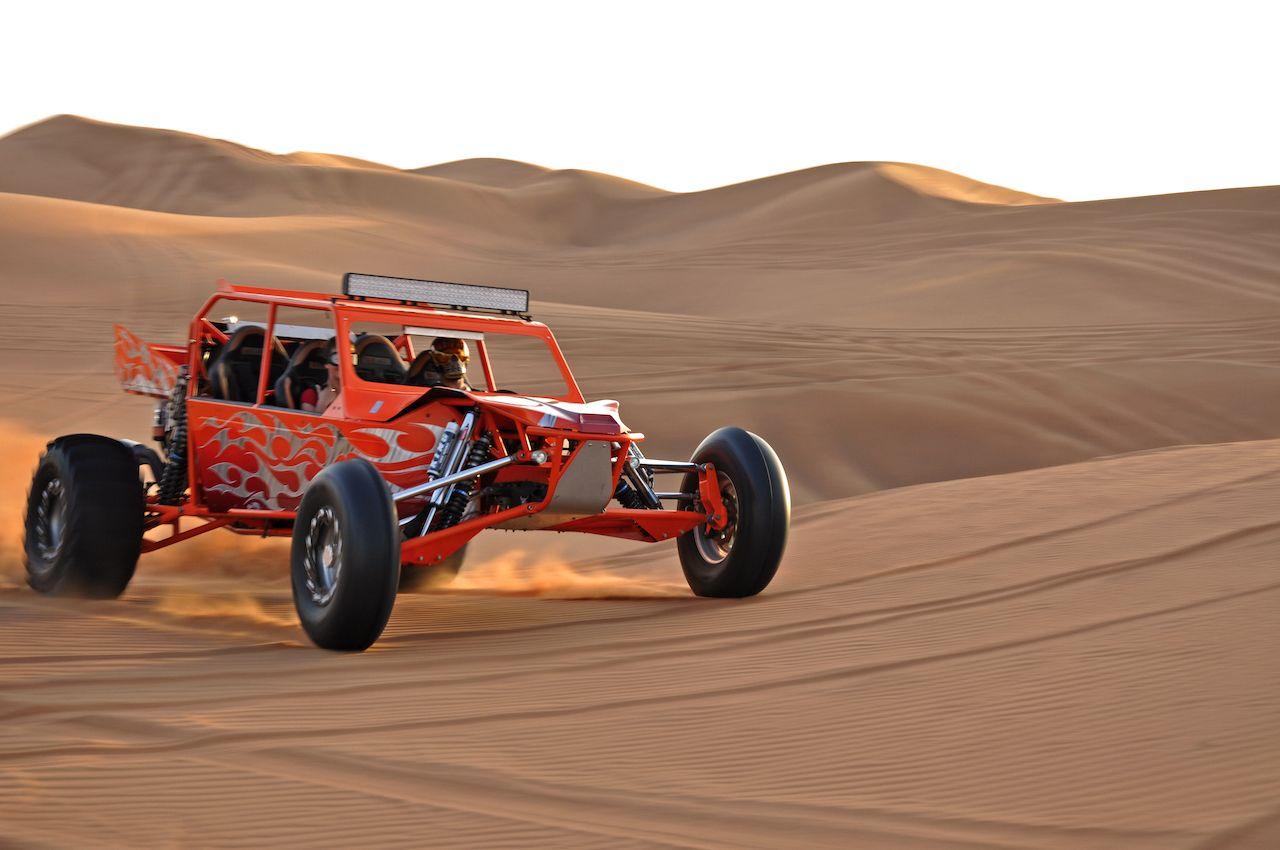 Tourist driving dune buggy in desert near Dubai, UAE