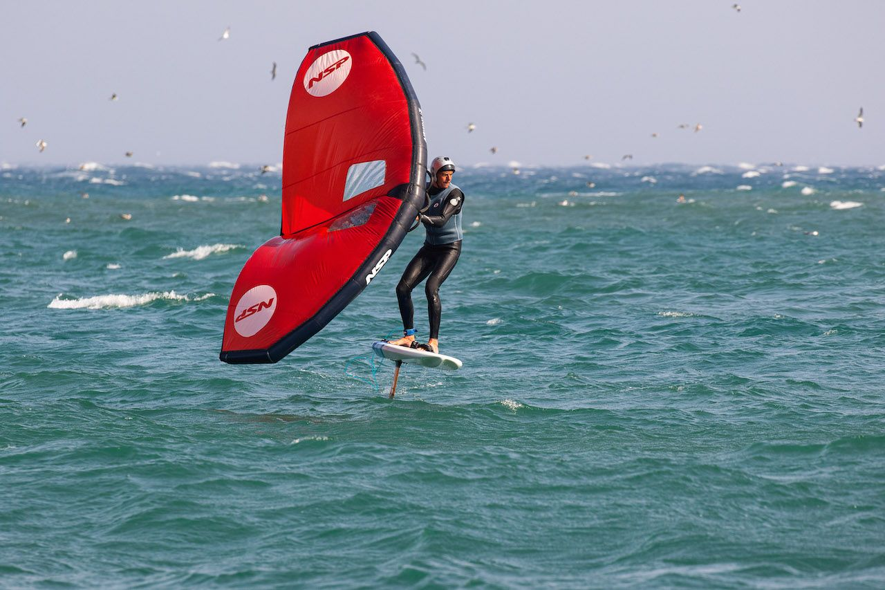 Wing foiler with wetsuit and helmet in Japan