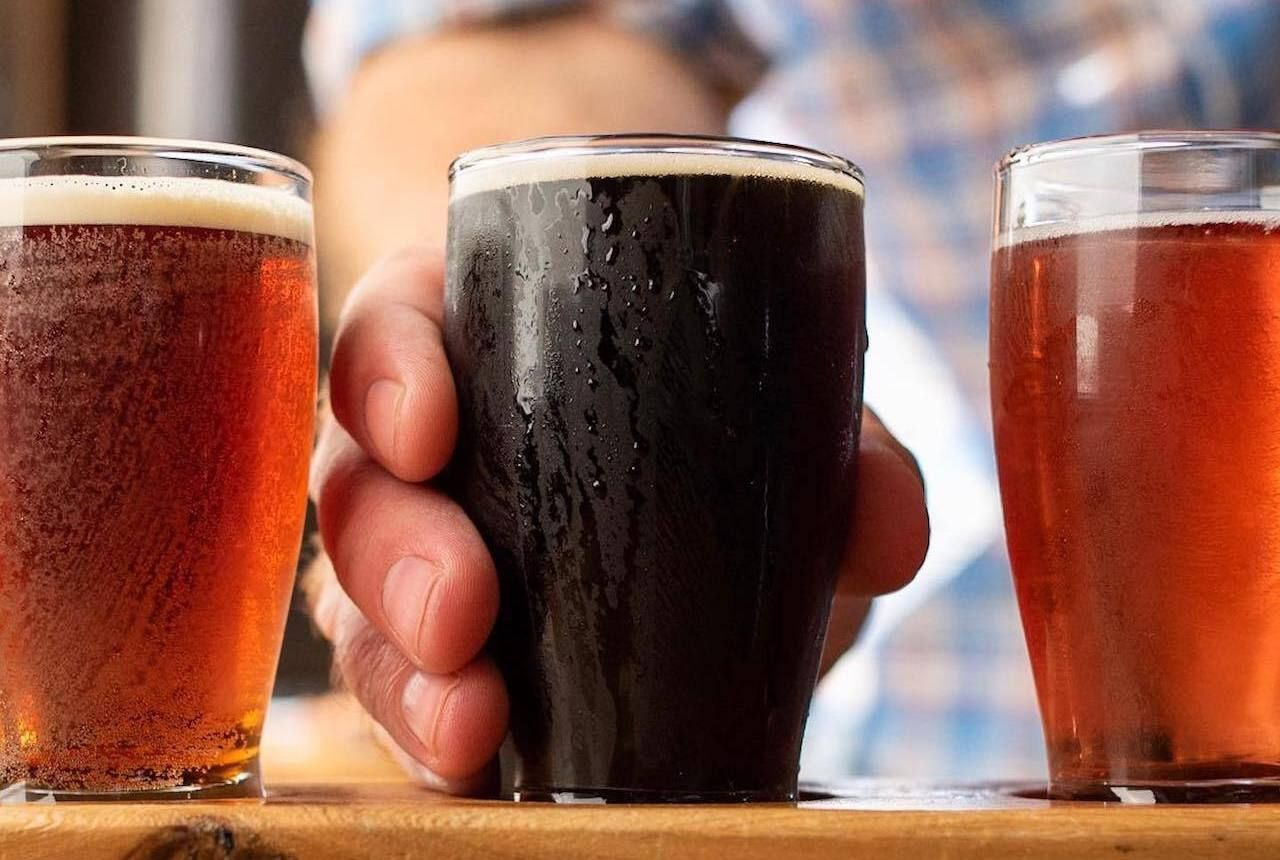 Selection of amber and dark beers and someone reaching for the dark beer at Penn Cove Brewing