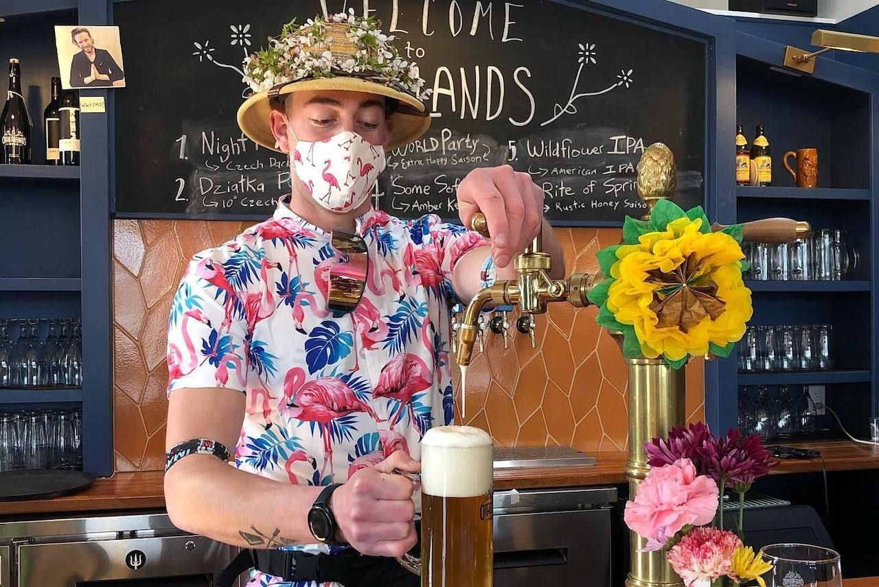 Bartender in bright shirt and flower-bedecked hat pours a pint at Otherlands Beer